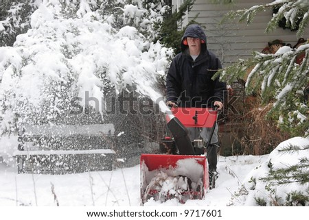 Man using a snow blower to clear a path after a storm - stock photo