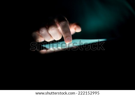 Man using a tablet in the dark navigating the glowing blue touchscreen with his finger , with copyspace. - stock photo