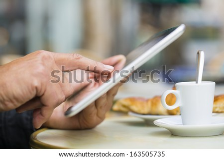 Man using a Tablet Pc on cafe terrace, croissant and coffee  - stock photo
