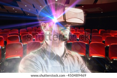 Man using a virtual reality device against empty rows of red seats - stock photo