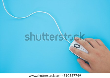 man using a white mouse on a blue background - stock photo