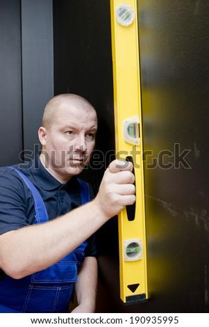 Man using a yellow spirit level on black wall - stock photo