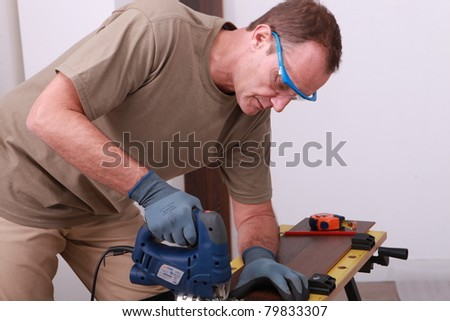 Man using an electric saw to cut a wooden floorboard - stock photo