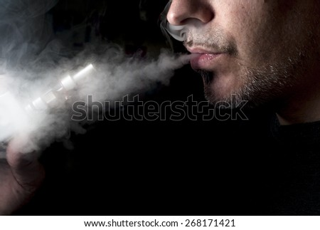 Man using an electronic cigarette, exhaling vapor; low key.  - stock photo