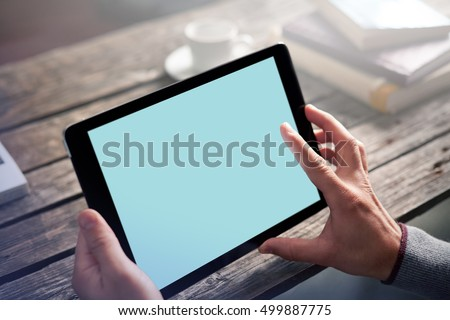 Man using app with digital tablet, sitting at cafe. Clipping path included.
