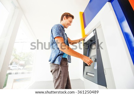 man using atm to withdraw cash - stock photo