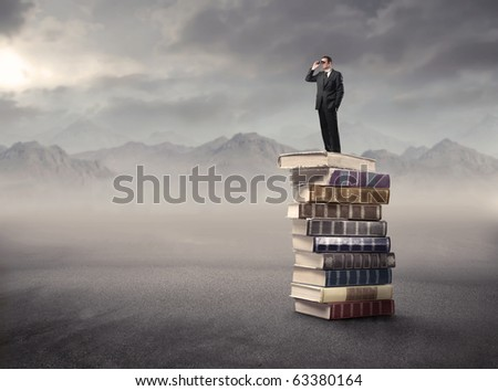 Man using binoculars standing on a stack of books in a desert - stock photo