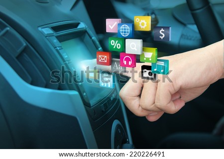 Man using car audio stereo system and pushing on car screen interface, With driver entering cloud of colorful application icon social media networking transportation and vehicle concept idea - stock photo