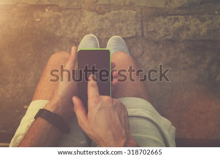 Man using cellphone outdoors. - stock photo