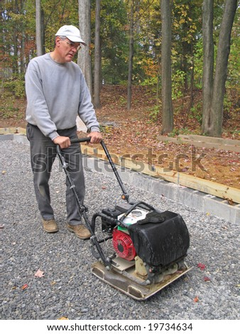 Man using compactor to pack stone to prepare for pouring a concrete slab - stock photo