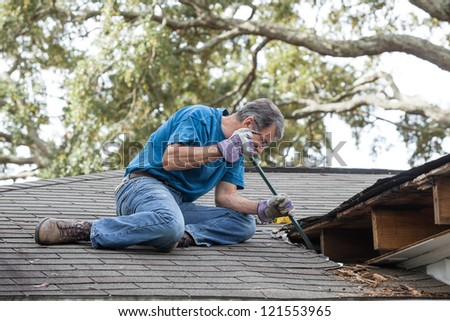 Man using crowbar to remove rotten wood from leaky roof. After removing fascia boards he has discovered that the leak has extended into the beams and decking. - stock photo