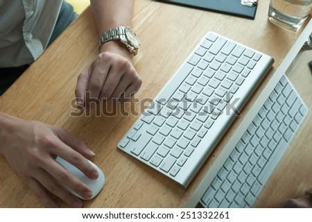 Man using desktop pc computer, mobile office concept - stock photo