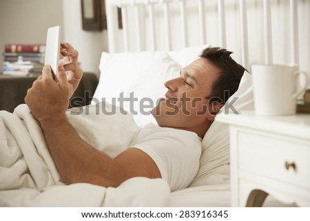 Man Using Digital Tablet In Bed At Home