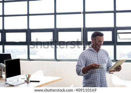 Man using digital tablet while having coffee in office - stock photo