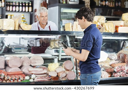 Man Using Digital Tablet While Salesman Packing Cheese - stock photo