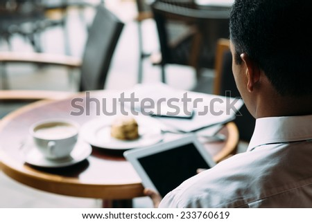 Man using digital tablet while sitting in the cafe, view over his shoulder - stock photo