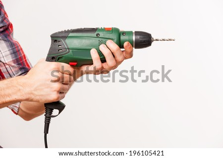Man using drill. Close-up side view of man using drill while standing against grey background - stock photo