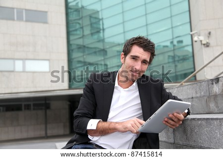 Man using electronic tablet in front of modern building - stock photo