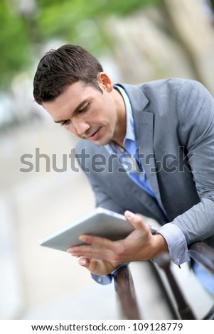 Man using electronic tablet outside in town - stock photo