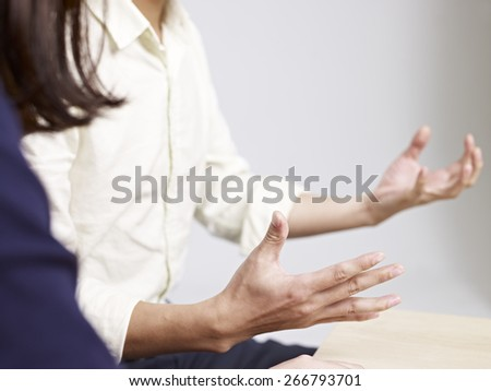 man using hand sign while talking to a woman. - stock photo