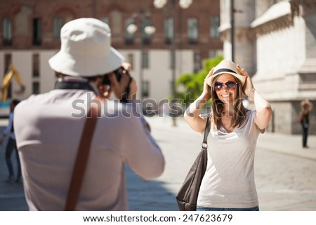 Man using his camera to take a picture of his girlfriend - stock photo