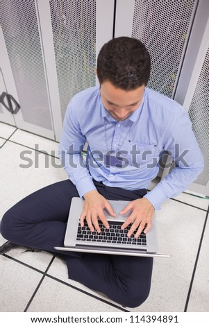 Man using his laptop in data center in front of servers - stock photo