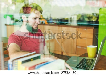 man using his laptop - view through the window - stock photo