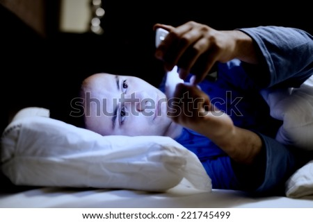 Man using his mobile phone in the bed - stock photo