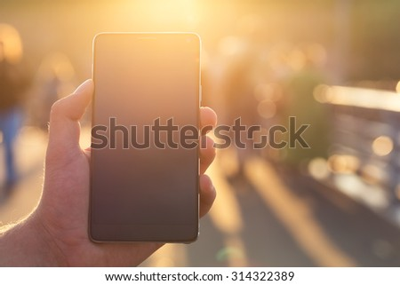 Man using his Mobile Phone outdoor, close up - stock photo