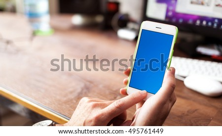 Man using his smartphone in his office. wooden desktop with blurry background. Blue empty display for copy space
