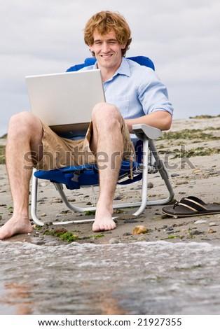Man using laptop at beach - stock photo
