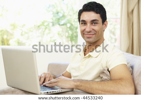 Man Using Laptop At Home - stock photo