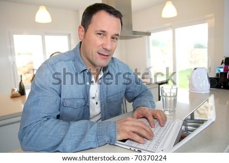 Man using laptop computer in kitchen - stock photo