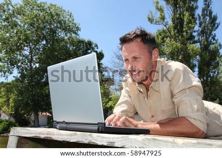 Man using laptop computer on a pontoon - stock photo