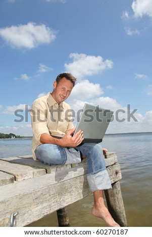 Man using laptop computer on a pontoon