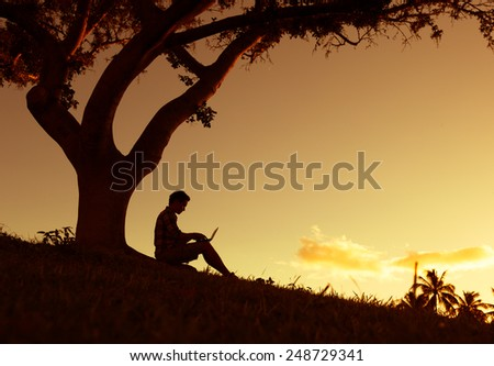 Man using laptop computer outdoors - stock photo