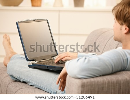 Man using laptop computer sitting on sofa in living room with feet up. - stock photo