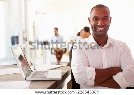 Man Using Laptop In Modern Office Of Start Up Business - stock photo