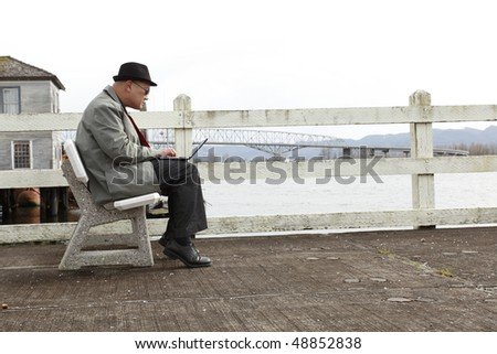 Man using laptop on the pier.