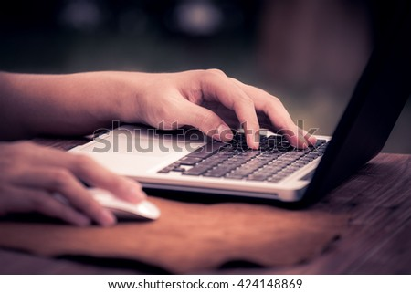 Man using laptop on wooden table outdoor, selective focus on left hand - stock photo