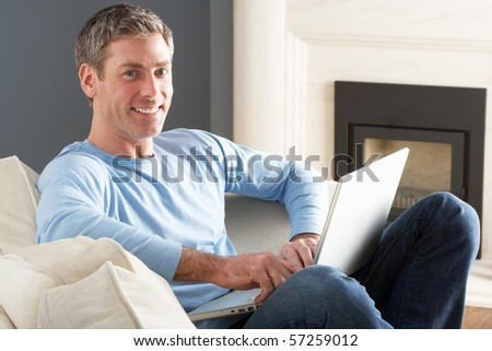 Man Using Laptop Relaxing Sitting On Sofa At Home - stock photo