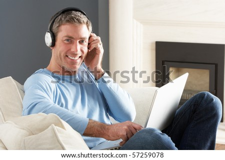 Man Using Laptop Wearing Headphones Relaxing Sitting On Sofa At Home - stock photo