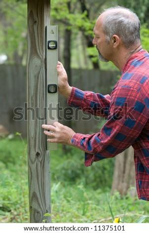 Man using level on post - stock photo