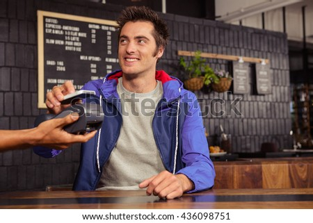 Man using mobile payment in a coffee shop - stock photo