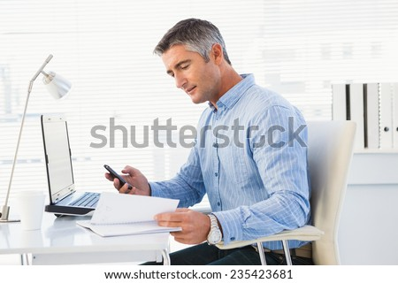 Man using mobile phone and looking in notebook in his office - stock photo