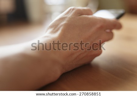man using mobile phone on table - stock photo