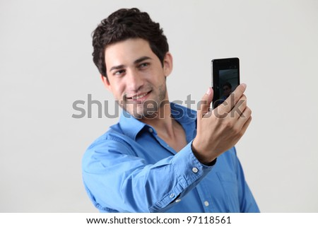 man using mobile phone to take a picture of himself - stock photo