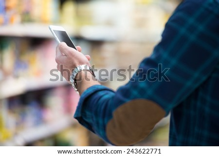 Man Using Mobile Phone While Shopping In Shopping Store - stock photo