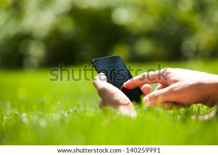 Man using mobile smart phone outdoor in summer
