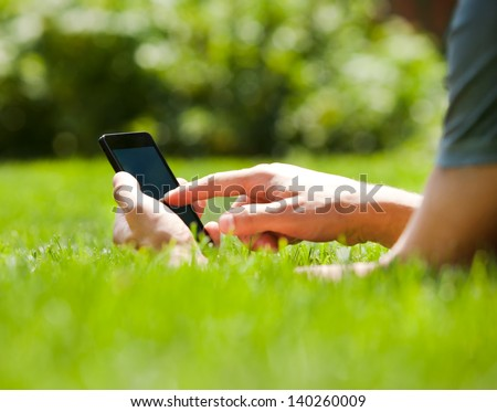 Man using mobile smart phone outdoor in summer - stock photo